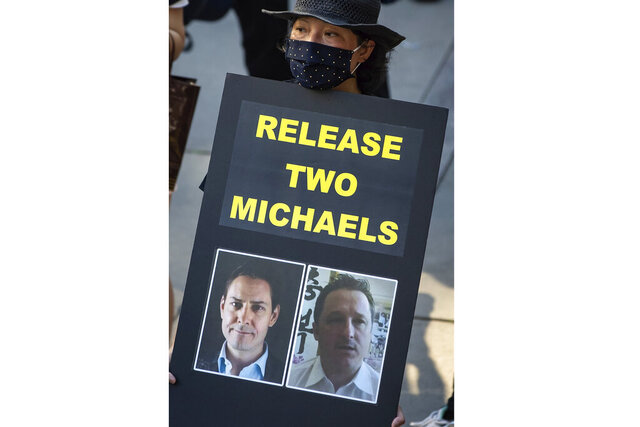 FILE - In this Aug. 16, 2020, file photo, a woman holds a sign with photographs of Michael Kovrig and Michael Spavor, who have been detained in China since December 2018, during a rally in support of Hong Kong democracy, in Vancouver, British Columbia. China's Foreign Ministry says two Canadians held for two years in a case linked to a Huawei executive have been indicted and tried, but gave no details. (Darryl Dyck/The Canadian Press via AP, File)