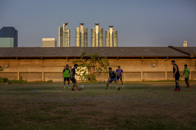 Thai man, some with face masks play a game of soccer in an open lot in Bangkok, Thailand, Wednesday, April 8, 2020. Playgrounds and public parks remained closed as a month-long state of emergency has been enforced in Thailand to allow its government to impose stricter measures to control the coronavirus that has infected hundreds of people in the Southeast Asian country. (AP Photo/Gemunu Amarasinghe)