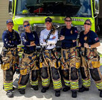 In this Sept. 19, 2020, photo provided by Palm Beach Gardens Fire and Rescue, firefighters Lt. Krystyna Krakowski, Lt. Kelsey Krzywada, fire medic Julie Dudley, lieutenant and acting Capt. Monica Marzullo and driver  engineer Sandi Ladewskipose at their station in Palm Beach Gardens, Fla. (Kodi Cabral/Courtesy of Palm Beach Gardens Fire and Rescue via AP)