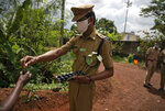 A policeman wearing mask to protect from the coronavirus hands out saplings to plant on World Environment Day in Kochi, Kerala state, India, Friday, June 5, 2020. (AP Photo/R S Iyer)