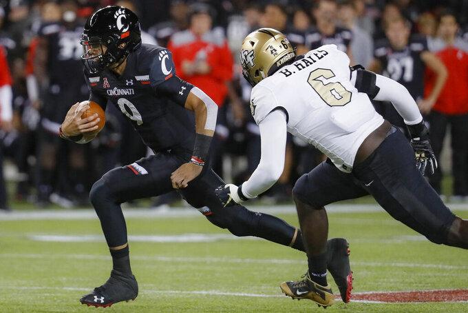 Cincinnati quarterback Desmond Ridder (9) runs the ball past UCF defensive lineman Brendon Hayes (6) during the first half of an NCAA college football game Friday, Oct. 4, 2019, in Cincinnati. (AP Photo/John Minchillo)