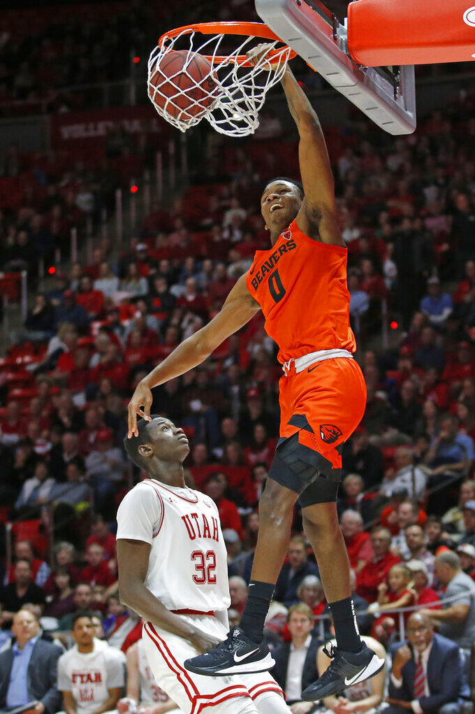 Oregon State guard Gianni Hunt (0) dunks on Utah center Lahat Thioune (32) in the first half during an NCAA college basketball game Thursday, Jan. 2, 2020, in Salt Lake City. (AP Photo/Rick Bowmer)