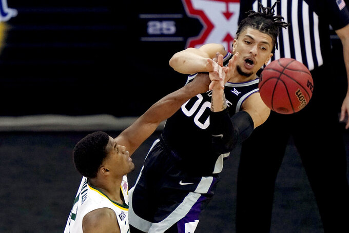 Kansas State's Mike McGuirl (00) passes under pressure from Baylor's Jared Butler during the second half of an NCAA college basketball game in the second round of the Big 12 men's tournament in Kansas City, Mo., Thursday, March 11, 2021. (AP Photo/Charlie Riedel)