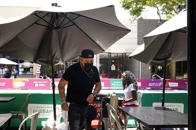 A waiter wears a face mask while tending to customers amid the COVID-19 pandemic Tuesday, May 18, 2021, in Burbank, Calif. (AP Photo/Marcio Jose Sanchez)
