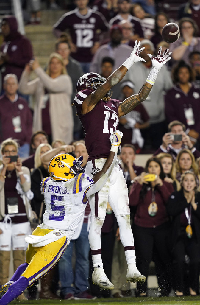 Texas A&M wide receiver Kendrick Rogers (13) catches a touchdown pass as LSU cornerback Kary Vincent Jr. (5) defends during overtime of an NCAA college football game Saturday, Nov. 24, 2018, in College Station, Texas. Texas A&M won 74-72 in seven overtimes.(AP Photo/David J. Phillip)