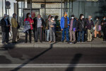People wear face masks to protect from coronavirus as they wait for a bus in Barcelona, Spain, Friday, Oct. 23, 2020. Spain has reported 1 million confirmed infections — the highest number in Western Europe — and at least 34,000 deaths from COVID-19, although experts say the number is much higher since many cases were missed because of testing shortages and other problems. (AP Photo/Emilio Morenatti)
