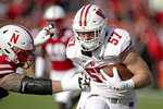 Wisconsin linebacker Jack Sanborn (57) carries the ball against Nebraska running back Dedrick Mills, left, after intercepting a pass by quarterback Adrian Martinez in the first half of an NCAA college football game in Lincoln, Neb., Saturday, Nov. 16, 2019. (AP Photo/Nati Harnik)