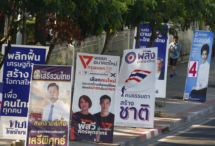 In this March 12, 2019, photo, a pedestrian walks past the election campaign posters in Bangkok, Thailand. Thailand heads to the polls Sunday, March 24, 2019 to vote in the country's first general election since the military toppled an elected government in a coup nearly five years ago. (AP Photo/Sakchai Lalit)