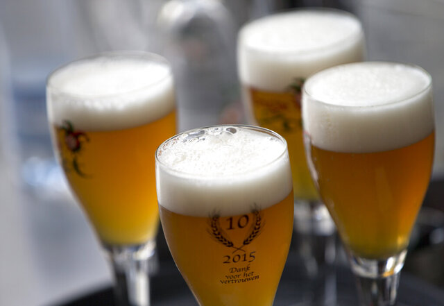 FILE - In this Thursday, May 26, 2016 file photo, glasses of beer stand on a serving tray in Bruges, Belgium. A university research survey has found that alcohol consumption in Belgium is remaining mostly stable during the country's coronavirus lockdown. A team of researchers at the University of Louvain said Wednesday, April 29,2020 that only one out of four respondents in their online survey this month reported drinking more while confined at home. (AP Photo/Virginia Mayo, File)