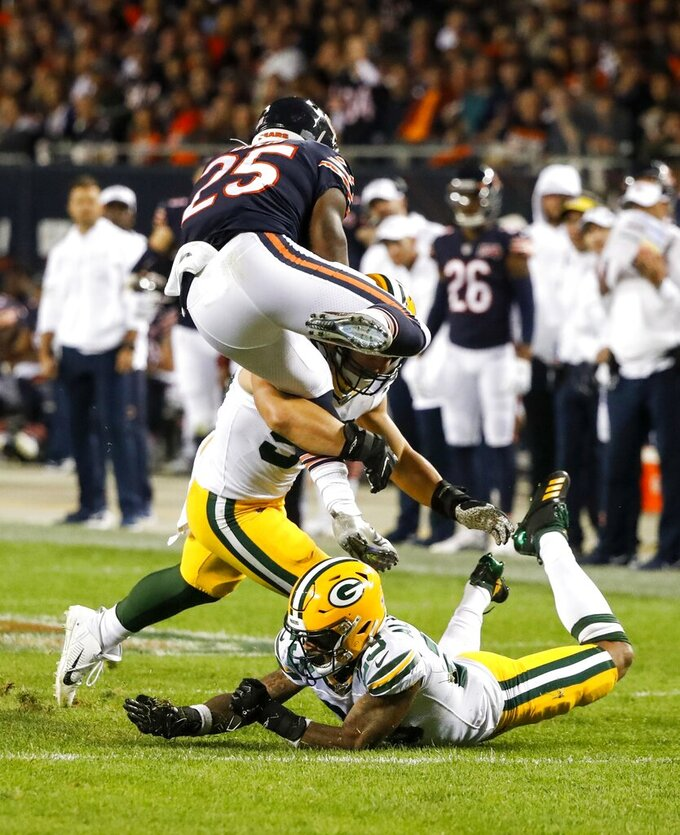 Chicago Bears' Mike Davis tries to leap over Green Bay Packers' Blake Martinez and Jaire Alexander during the first half of an NFL football game Thursday, Sept. 5, 2019, in Chicago. (AP Photo/Charles Rex Arbogast)