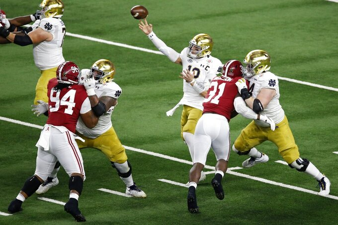 Alabama defensive lineman DJ Dale (94) linebacker Will Anderson Jr. (31) rush as Notre Dame quarterback Ian Book (12) throws a pass in the first half of the Rose Bowl NCAA college football game in Arlington, Texas, Friday, Jan. 1, 2021. (AP Photo/Roger Steinman)
