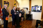 Maryland Assistant State Attorney Patrick Seidel, second from left, stands next to State Attorney Marilyn Mosby, third from right, as a monitor displays two of the correction officers indicted during a news conference, Tuesday, Dec. 3, 2019, in Baltimore. Twenty five correction officers, most of whom were taken into custody earlier in the day, are charged with using excessive force on detainees at state-operated Baltimore pretrial correctional facilities. (AP Photo/Julio Cortez)