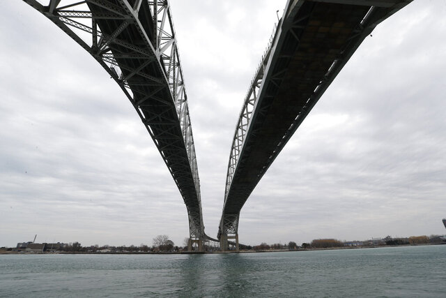 The twin spans of the Blue Water Bridge loom over the St. Clair River in Port Huron, Mich., looking to Sarnia, Ontario, Canada, Wednesday, March 18, 2020. The Canada-U.S. border will be closed to non-essential traffic in both directions