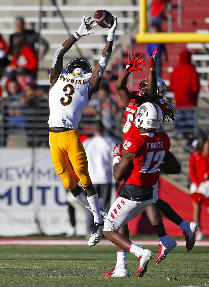 Wyoming strong safety Alijah Halliburton (3) breaks up a pass intended for New Mexico wide receiver Emmanuel Harris (6) as Anu Somoye (12) looks on during the second half of an NCAA college football game in Albuquerque, N.M., Saturday, Nov. 24, 2018. Wyoming won 31-3. (AP Photo/Andres Leighton)
