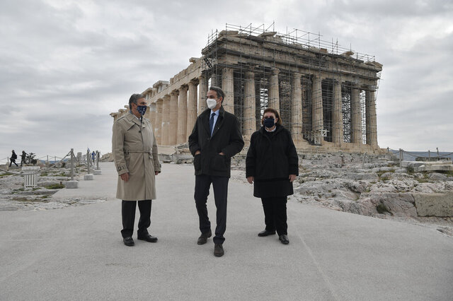 Greek Prime Minister Kyriakos Mitsotakis, center, Culture Minister Lina Mendoni, right, and President of the Onassis Foundation, Antonis Papadimitriou, stand in front of the of the Parthenon Temple, following the restoration of the Acropolis archaeological site in order to become fully accessible to people with disabilities and mobility issues, during the International Day of Persons with Disabilities, in Athens, on Thursday, Dec. 3, 2020. (Louisa Gouliamaki/Pool via AP)