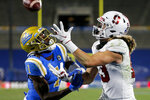 Stanford wide receiver Simi Fehoko (13) catches a pass in the end zone for a touchdown while defended by UCLA defensive back Jay Shaw (1) during overtime of an NCAA college football game Saturday, Dec. 19, 2020, in Pasadena, Calif.  Stanford won 48-47 in overtime. (AP Photo/Ringo H.W. Chiu)