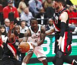 Milwaukee Bucks guard Eric Bledsoe, center, makes a pass as Portland Trail Blazers forward Al-Farouq Aminu, left, and center Jusuf Nurkic, right defend during the first half of an NBA basketball game in Portland, Ore., Tuesday, Nov. 6, 2018. (AP Photo/Steve Dipaola)