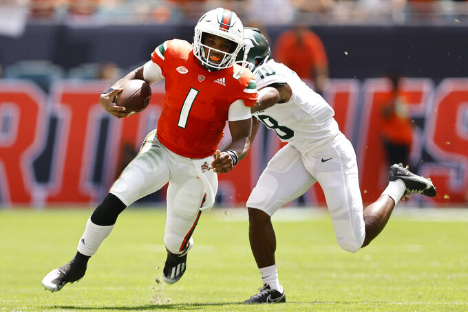 Miami quarterback D'Eriq King (1) breaks a tackle from Michigan State cornerback Kalon Gervin (18) during the second quarter of an NCAA college football game, Saturday, Sept. 18, 2021, in Miami Gardens, Fla. (AP Photo/Michael Reaves)