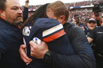 Virginia head coach Bronco Mendenhall, right, buries his head in the shoulder of Virginia quarterback Bryce Perkins (3) as he and his team celebrate beating Virginia Tech after an NCAA college football game between Virginia Tech and Virginia in Charlottesville, Va., Friday, Nov. 29, 2019. Virginia defeated Virginia Tech 39-30 for the first time in 15 years. (AP Photo/Steve Helber)