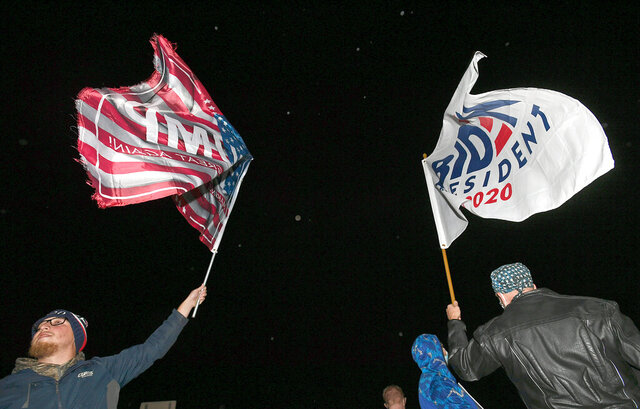 On West 12th Street across from the Erie International Airport, Steven Lantz-Gordon, 24, at left, of Harborcreek Township, waves a flag in support of President Donald Trump near David Oberg, 60, at right, of Grand Valley, who raises a flag in support of Democratic presidential candidate and former Vice President Joe Biden during a rally held by Trump, Tuesday, Oct. 20, 2020, at Erie International Airport, Tuesday, Oct. 20, 2020, in Millcreek Township, Pa. (Christopher Millette/Erie Times-News via AP)