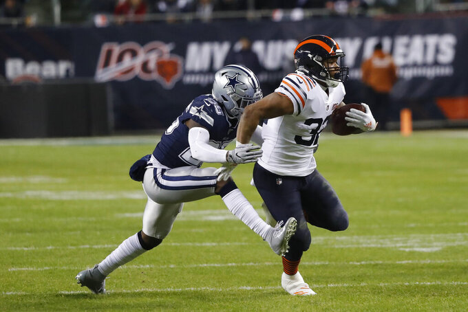 Chicago Bears' David Montgomery (32) is tackled by Dallas Cowboys' Xavier Woods (25) during the first half of an NFL football game, Thursday, Dec. 5, 2019, in Chicago. (AP Photo/Charles Rex Arbogast)