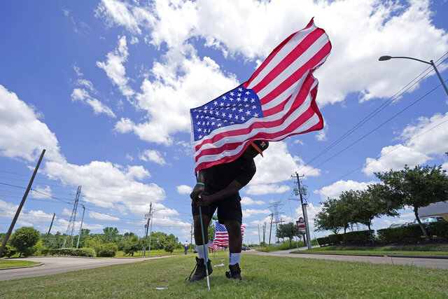 Bryan Smart plants United States flags along Hillcroft Avenue as he walks toward The Fountain of Praise church Sunday, June 7, 2020, in Houston. A public memorial and private funeral service for George Floyd will be held at the church. Floyd died after being restrained by Minneapolis police officers on May 25. (AP Photo/David J. Phillip