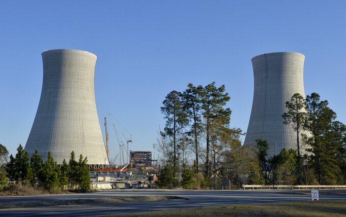 FILE - In this March 22, 2019 file photo, the cooling towers of the still under construction Plant Vogtle nuclear energy facility are seen in Waynesboro, Ga. Georgia Power Co. has filed for a $235 million annual rate increase to help pay for its $11.8 billion share of the $26 billion project to build two new nuclear reactors at the complex near Augusta, Ga. (Michael Holahan/The Augusta Chronicle via AP, File)