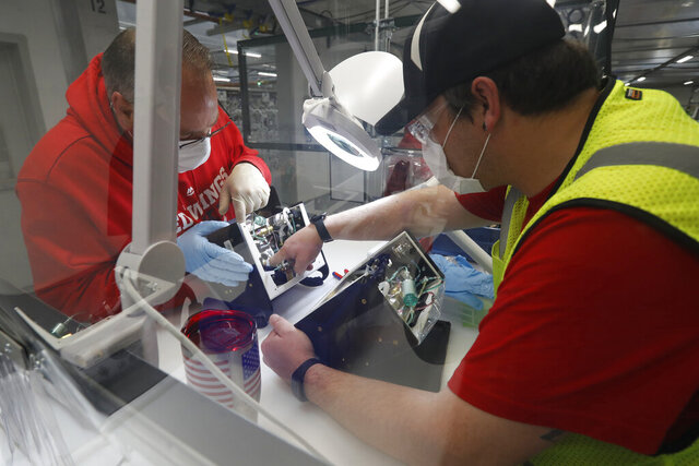 FILE - In this Wednesday, May 13, 2020 file photo, Ford Motor Co. employees work a ventilator at the Rawsonville plant in Ypsilanti Township, Mich. The plant was converted into a ventilator factory, as hospitals battling the coronavirus report shortages of the life-saving devices. According to the Institute for Supply Management, U.S. manufacturing rebounded in June 2020 as major parts of the country opened back up, ending three months of contraction in the sector caused by the coronavirus pandemic. (AP Photo/Carlos Osorio)