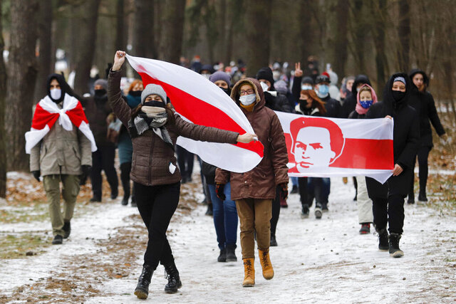 Demonstrators wearing face masks to help curb the spread of the coronavirus carry old Belarusian national flags during an opposition rally to protest the official presidential election results in Minsk, Belarus, Sunday, Dec. 13, 2020. Protests in Belarus have continued for almost four months after President Alexander Lukashenko won his sixth term in office in an election the opposition says was rigged. (AP Photo)