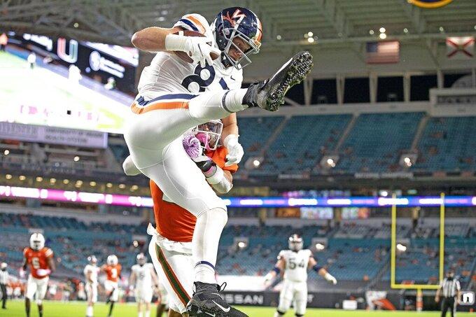 Virginia's Tony Poljan (87) catches a first-quarter touchdown as Miami's Bubba Bolden fails to defend during an NCAA college football game in Miami Gardens, Fla., Saturday, Oct. 24, 2020. (Al Diaz/Miami Herald via AP)