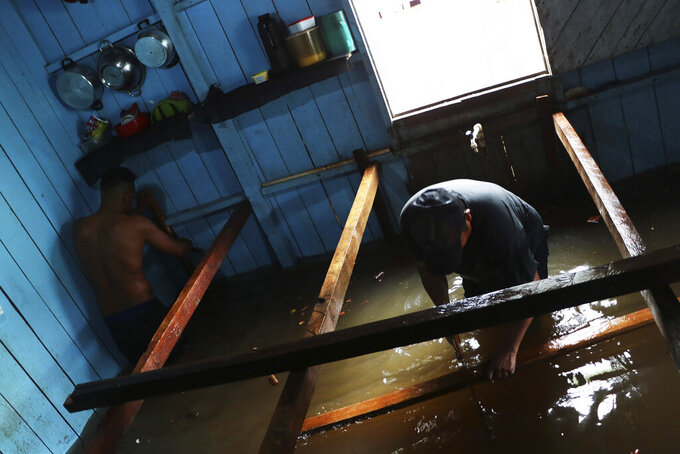 Residents build raised floors in a flooded home in Anama, Amazonas state, Brazil, Thursday, May 13, 2021. (AP Photo/Edmar Barros)