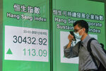 A man wearing a face mask walks past a bank's electronic board showing the Hong Kong share index in Hong Kong, Tuesday, Feb. 23, 2021. Asian shares were mostly higher on Tuesday despite a sell-off in technology companies on Wall Street. (AP Photo/Kin Cheung)