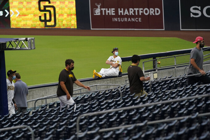 San Diego Padres center fielder Wil Myers, center, keeps his distance as other members of the Padres walk into the stands for a team meeting after their baseball game against the San Francisco Giants was postponed Friday, Sept. 11, 2020, in San Diego, after someone in the Giants organization tested positive for COVID-19. (AP Photo/Gregory Bull)