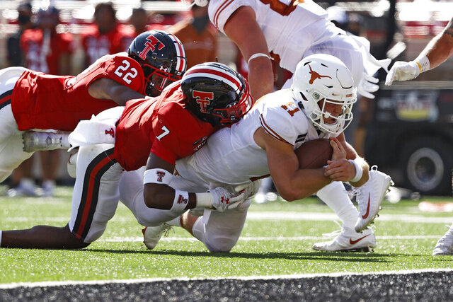Texas' Sam Ehlinger (11) is tackled by Texas Tech's Adrian Frye (7) short of the goal line during the first half of an NCAA college football game Saturday, Sept. 26, 2020, in Lubbock, Texas. (Brad Tollefson/Lubbock Avalanche-Journal via AP)