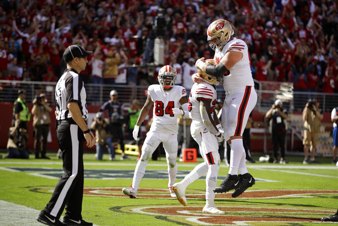 San Francisco 49ers running back Tevin Coleman is greeted by teammate offensive guard Mike Person, top, after scoring a touchdown during the first half of an NFL football game against the Carolina Panthers in Santa Clara, Calif., Sunday, Oct. 27, 2019. In the background is San Francisco 49ers wide receiver Kendrick Bourne (84). (AP Photo/Ben Margot)