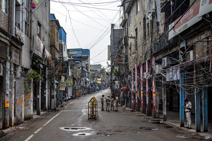 Indian Home Guard personnel stand in an empty street of Sadar Bazar wholesale market which is partially closed for violating COVID-19 guidelines in New Delhi, India, Tuesday, July 13, 2021. (AP Photo/Altaf Qadri)