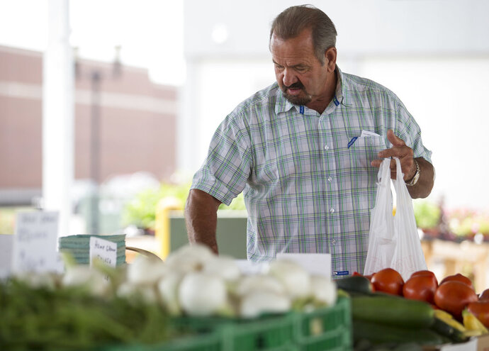 FILE- In this June 13, 2018, file photo, Bob Harris carefully selects which tomatoes to buy at Paducah, Kentucky's Downtown Farmers' Market. On Thursday, July 12, the Labor Department reports on U.S. consumer prices for June. (Ellen O'Nan/The Paducah Sun via AP, File)