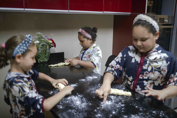 Musya Banon, right, and her sisters Nina, left, and Sara, center, bake challah bread for Shabbat, in their home in Casablanca, Morocco, Thursday, May 28, 2020. (AP Photo/Mosa'ab Elshamy)