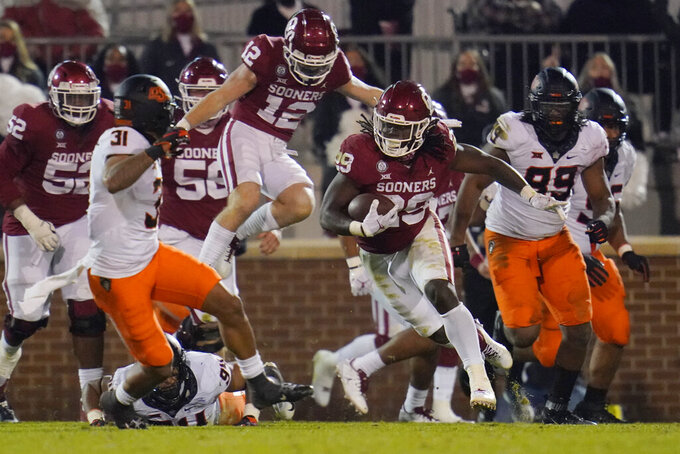 Oklahoma running back Rhamondre Stevenson (29) carries against Oklahoma State during the second half of an NCAA college football game in Norman, Okla., Saturday, Nov. 21, 2020. (AP Photo/Sue Ogrocki)