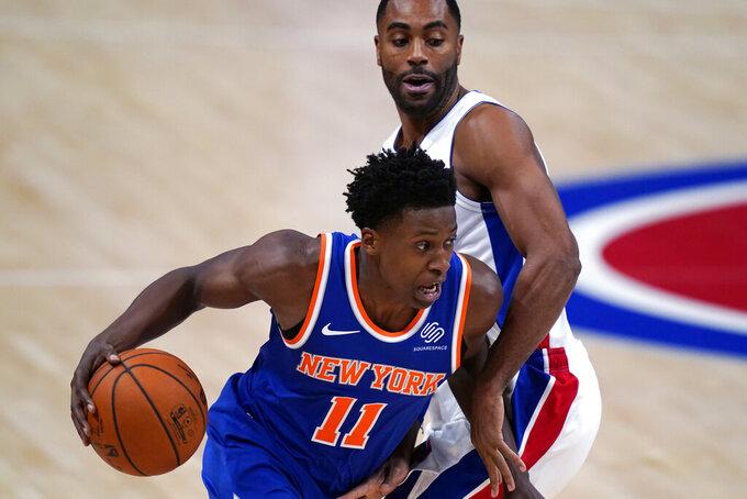 New York Knicks guard Frank Ntilikina (11) drives around Detroit Pistons guard Wayne Ellington during the first half of a preseason NBA basketball game Friday, Dec. 11, 2020, in Detroit. (AP Photo/Carlos Osorio)