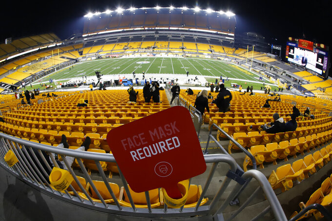 "A ""Face Mask Required"" sign is posted behind the limited number of fans attending an NFL wild-card playoff football game between the Pittsburgh Steelers and the Cleveland Browns, Sunday, Jan. 10, 2021, in Pittsburgh. (AP Photo/Keith Srakocic)"