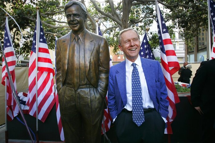 FILE - In this Aug. 25, 2007, file photo, former California Gov. Pete Wilson imitates the pose of a statue dedicated in his honor at Horton Plaza in San Diego. The statue was removed from the park after critics said the governor supported laws and policies that hurt immigrants and LGBTQ community members, the San Diego Union-Tribune reported Thursday, Oct. 16, 2020.  (Nelvin Cepeda/The San Diego Union-Tribune via AP)