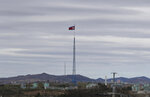 FILE - In this April 27, 2018, file photo, a North Korean flag flutters in the wind atop a 160-meter tower in North Korea's village Gijungdongseen, as seen from the Taesungdong freedom village inside the demilitarized zone in Paju, South Korea. North Korea says the son of the highest-profile South Korean ever to defect to the North has arrived there to permanently resettle. (AP Photo/Lee Jin-man, File)