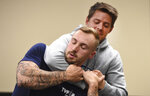 In this photo taken Sept. 10, 2019, Ryan Russo, left, and Mike Herrall go through a drill during a defensive tactic training class at the American Medical Response training center in Clackamas, Ore. Paramedics in Portland are undergoing mandatory training in defensive tactics after a rash of high-profile attacks against them as they respond to 911 calls for people in a mental health or drug-related crisis. (AP Photo/Steve Dykes)