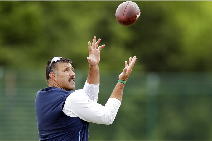 Tennessee Titans head coach Mike Vrabel catches a ball thrown to him during an organized team activity at the Titans' NFL football training facility Thursday, May 30, 2019, in Nashville, Tenn. (AP Photo/Mark Humphrey)