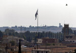 FILE - In this Oct. 22, 2019 photo taken from the Turkish side of the border between Turkey and Syria, in Akcakale, Sanliurfa province, southeastern Turkey, Syria's opposition flag flies on a pole in Tal Abyad, Syria.  Turkey's Defense Ministry says a car bomb went off in Tal Abyad, killing several civilians. The ministry says others were wounded when the bomb exploded Saturday, Nov. 2 in central Tal Abyad, which was captured last month by Turkey-backed opposition gunmen from Kurdish-led fighters.  (AP Photo/Lefteris Pitarakis, File)