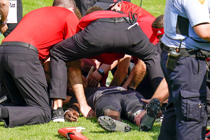 Trainers tend to Louisville quarterback Malik Cunningham (3) after he was injured during the second half of an NCAA college football game Pittsburgh, Saturday, Sept. 26, 2020, in Pittsburgh. (AP Photo/Keith Srakocic)