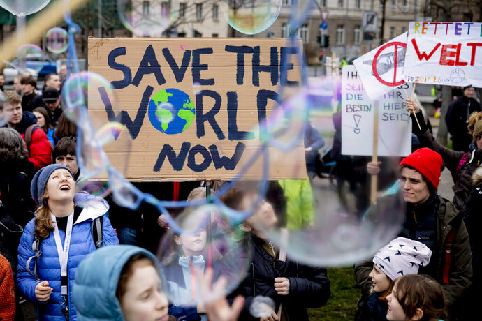 Young people protest for climate action with a sign reading 'Save the World Now