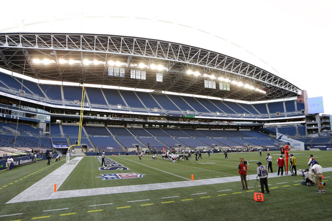 The Seattle Seahawks and New England Patriots play during the first half of an NFL football game in an empty CenturyLink Field stadium Sunday, Sept. 20, 2020, in Seattle. No fans were in attendance due to the coronavirus pandemic. (AP Photo/John Froschauer)