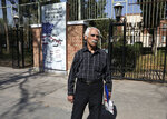 In this Tuesday, Oct. 15, 2019 photo, Hossein Kouhi, who was one of the workers who frequently protested at the U.S. Embassy, speaks with an Associated Press journalist, in front of the former U.S. Embassy in Tehran, Iran. As the former embassy's shaded red brick walls were in the process of being painted with anti-U.S. murals for the upcoming anniversary of the hostage crisis, Kouhi said he turned out in 1979 to denounce what he called U.S. intervention in Iran's internal affairs, something he says continues today.  (AP Photo/Vahid Salemi)